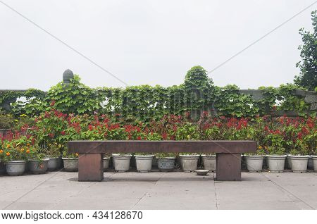 A Stone Bench With Potted Plants Against A Railing And Overcast Sky On Top Of Mount Wuyou In Leshan
