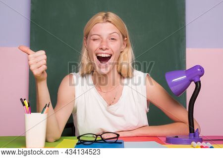 Learn With Fun. Funny Female Teacher Sitting At Her Workplace And Teaching English. Happy Funny Teac
