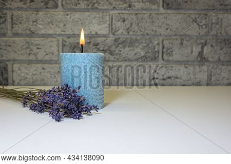 Dry Lavender Bunch Near A Burning Candle On The Background Of A Blurred Gray Brick Wall In The Inter