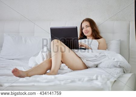 Bare Woman In Bed During Teleworking With Laptop.