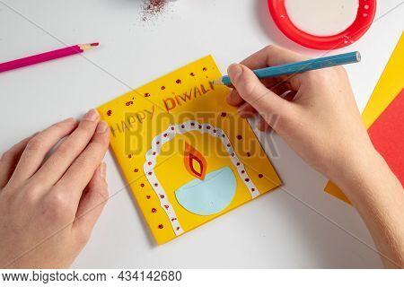 Happy Diwali Concept. A Faceless Child Makes A Postcard With A Bowl Of Fire. Various Materials For C