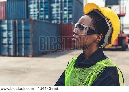 Young African American Woman Worker At Overseas Shipping Container Yard . Logistics Supply Chain Man