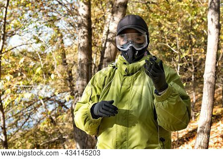 A Woman Wearing A Respirator Mask, Protective Glasses And Rubber Gloves In The Forest At Covid-19 Pe