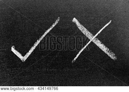 White Color Chalk Hand Drawing In Check Mark Of Right And Wrong Shape On Black Board Background
