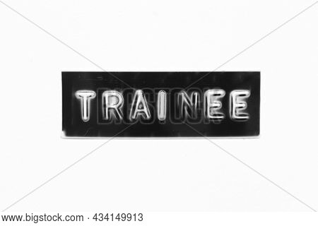 Black Color Banner That Have Embossed Letter With Word Trainee On White Paper Background