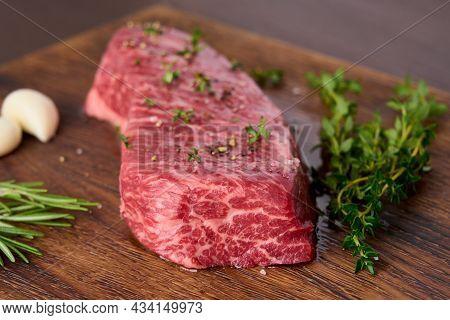 Raw Marble Striploin Steak With Thyme, Rosemary, Garlic, Salt, Pepper. Rustic Beef Tenderloin Meat O