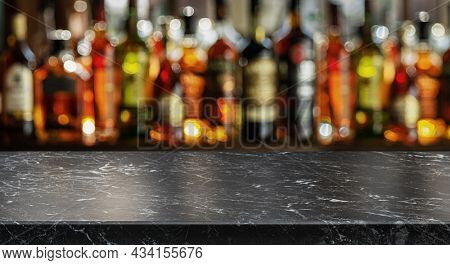 Grey table top and beautiful bokeh shelves with alcohol bottles at the background. Bar concept.