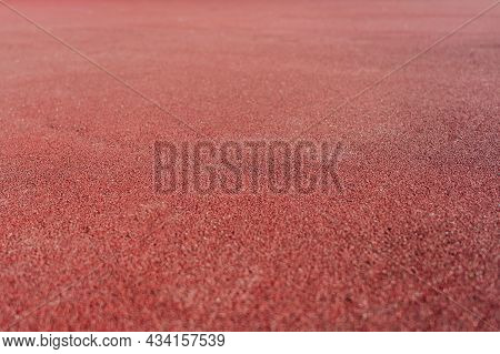 Red Rubber Coating Made Of Recycled Rubber Chips On The Sports Field. Selective Focus