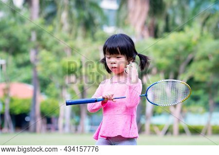 A Girl Holding A Badminton Racket And A Racquet, A Child Is A Insecure Expression Or Embarrassed Exp