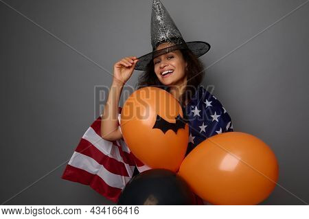 Cheerful Mixed Race Woman In Wizard Hat, Wrapped In American Flag, Holds Colorful Orange Air Balls,
