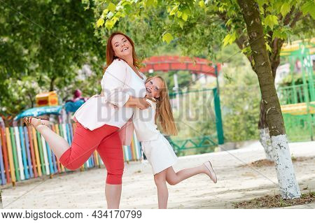 Littered Horizon. Family. Mother And Little Daughter, Hugging And Posing Merrily. Games In The Park.