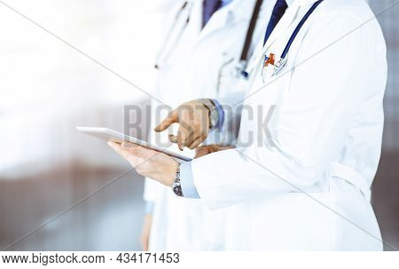 Two Unknown Doctors With Stethoscopes Discussing Medical Exam Resoults, Standing At Sunny Hospital O