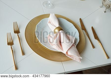 Festive Table Setting. Plates And Golden Cutlery With Pink Napkin On White Table. Beautiful Flat Lay