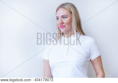 Attractive Blonde Woman In A White Polo Shirt Stands With Her Arms Folded On Her Chest Against The B
