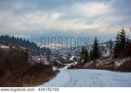 Empty Winter Road Leading To The Village Among The Mountains. Winter Landscape