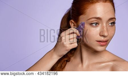Tender Beautiful Women With Red Hair, Glowing Clean Skin, Massaging Face With Jade Scraper And Smili