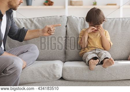 Child Abuse Concept. Unhappy Little Boy Sitting On Sofa And Crying, Unrecognizable Angry Father Scol
