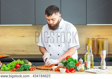 Young chef is cutting fish in a modern kitchen. The man prepares food at home. Cooking healthy and tasty food.
