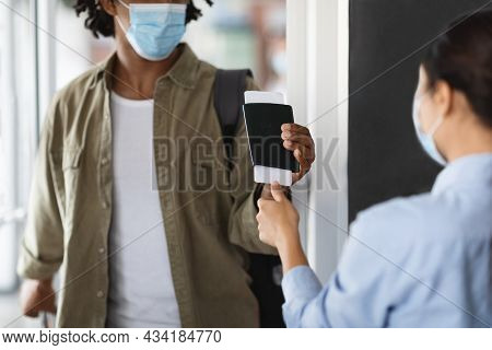 Black Traveller In Mask Having Passport And Tickets Control Checking At Airport