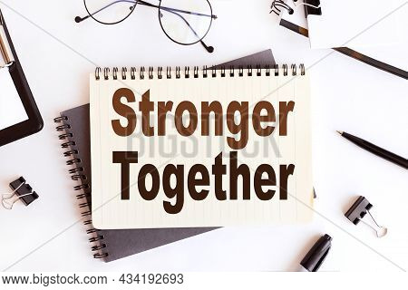 Stronger Together, Text On Notepad. On A White Background Near The Stationery