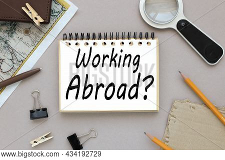 Work Abroad, Text On Notepad Near Magnifier And Card With Notepad