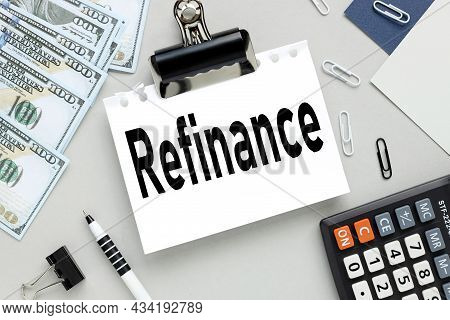 Refinance. Blank Sheet Of Paper On A Gray Background. Near The Bills Of Money And Beilnik.