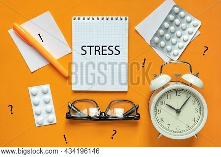 Blank Of Notepad With The Word Stress, Pen, Clock And Antidepressants On Orange Background. Top View