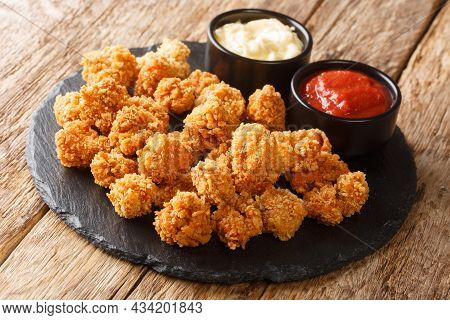 Spicy Chicken Popcorn Breaded Deep Fried Served With Two Sauces Close Up On A Slate Board On The Tab