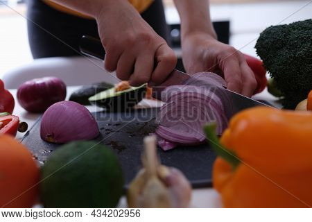 Woman Cuts Red Onion Into Wedges Closeup