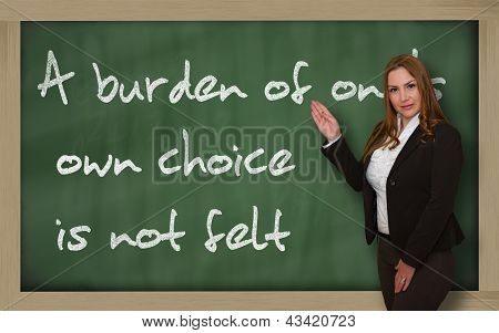 Teacher Showing A Burden Of One's Own Choice Is Not Felt On Blackboard