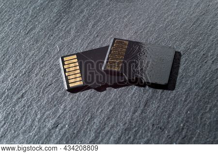 Two Micro Sd Cards Lie On Top Of Each Other On A Dark Textured Background, With Golden Contacts At T