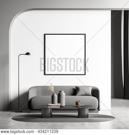 Square Canvas On The White Wall Of The Living Room Interior With An Archway Over A Grey Sofa. Modern