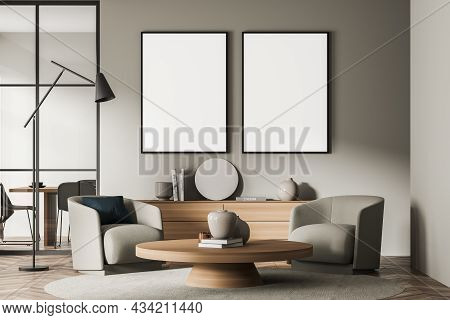 Two Canvases On The Beige Wall Of The Living Room Interior With A Sideboard And Armchairs In A Seati