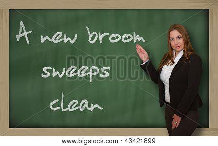 Teacher Showing A New Broom Sweeps Clean On Blackboard
