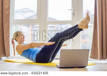 Beautiful Young Woman In Sportswear Doing Sport Exercises On Yoga Mat At Home. Fitness Training Onli