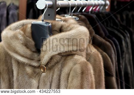 Fur Coats In A Row On A Hanger In The Store. Female Fashion, Natural Fur Clothes From Mink In Sale