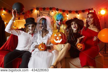 Group Of People In Halloween Costumes Sitting On Couch And Screaming At Fun Party At Home