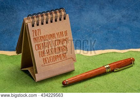 2021 - International Year of Creative Economy for Sustainable Development declared by United Nations, handwriting in desktop calendar against abstract paper landscape