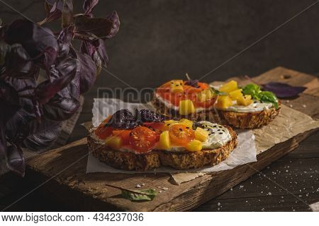 Italian Bruschettas With Roasted Tomatoes, Mozzarella Cheese, Pineapple Slices And Herbs On A Wooden