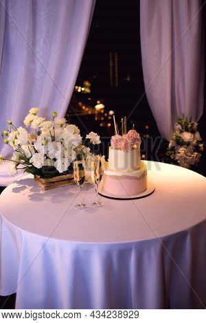 Wedding Cake With Glasses Of Champagne On The Table, Decorated With Fresh White Flowers. Wedding Eve