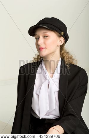 Portrait Of Cheerful Girl In Elegant Suit And Cap. Charming Stylish Young Woman In Fashionable Black