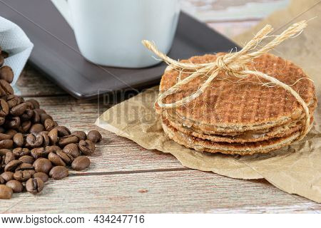 Closeup Of Stroopwafel Biscuits With A Sisal Bow Next To Coffee Beans.