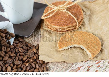 Closeup Of Stroopwafel Cookies With A Bite Next To Beans And Cup Of Coffee.