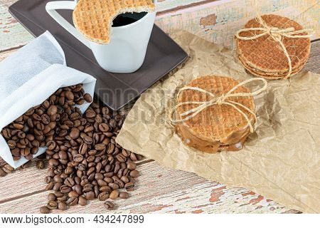 Stroopwafels Stacked On Brown Paper, Next To Beans And Cup Of Coffee.