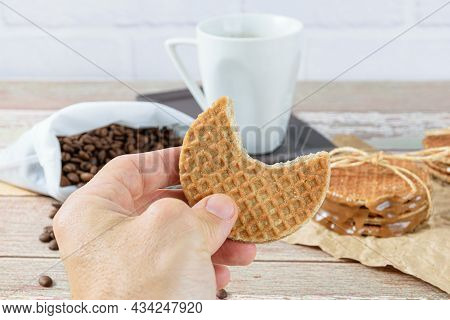 Man Holding A Stroopwafel With A Bite. In The Background Beans And Cup Of Coffee.