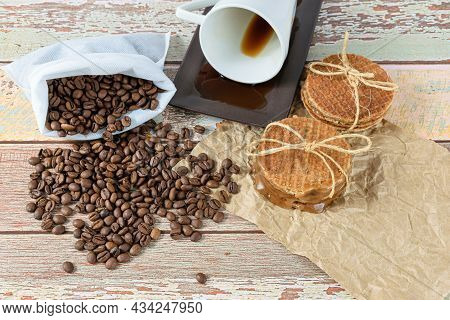 Stroopwafels Stacked On Brown Paper, Next To A Lying Coffee Cup (top View).