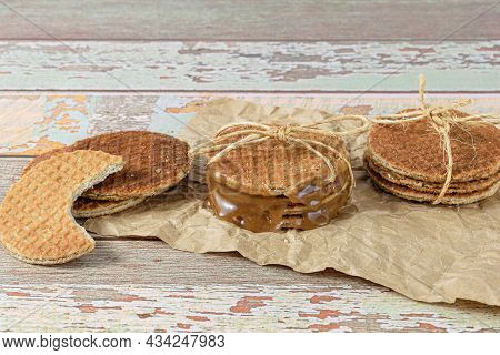 Stack Stroopwafels On Brown Paper, Next To Another Biscuit With A Bite (side View).