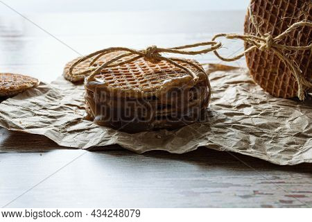 Low Key Photography. Closeup Of A Stack Of Stroopwafels With A Sisal Bow, Next To Other Cookies.