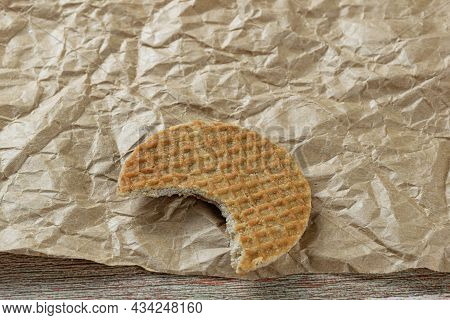 Stroopwafel Closeup With A Bite On A Brown Paper.
