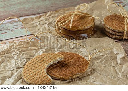 Stroopwafel With A Bite On Brown Paper Next To Another Cookie And Sisal String (side View).